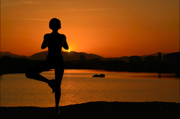 Girl doing yoga at sunset