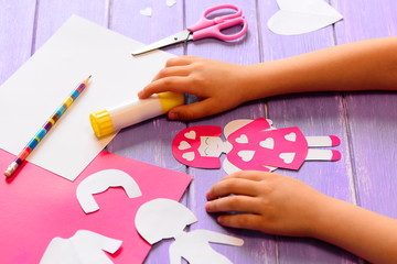 Small child made an angel doll of cardboard. Childrens hands on a wooden table. Craft supplies for a fun kids activity. Valentine's day crafts idea for kids in home or kindergarten