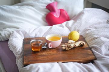 Verwöhnen bei Krankheit mit alternativen Hausmitteln wie Tee, Ingwer und Wärmflasche