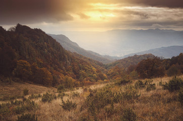 Photo sur Plexiglas Colline Sunset light in mountain landscape. Hills and forests seen from above in autumn scenery