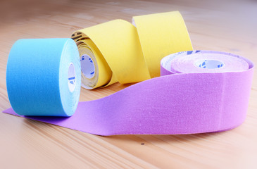 Special physio tape rolls on wooden background, closeup.