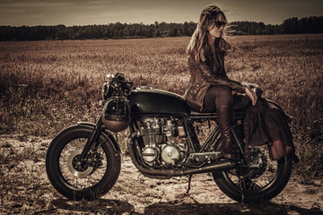 Young, stylish woman on vintage custom cafe racer in field