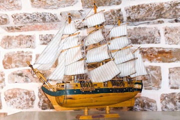 Miniature ship over brick background in museum near Budva, Montenegro, wooden replica of the old vessel sailfish