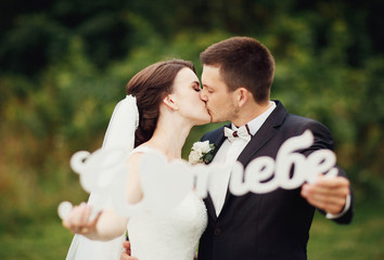 beautiful and young bride and groom kissing outdoors