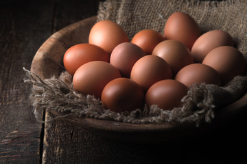Chicken eggs in the wooden bowl horizontal