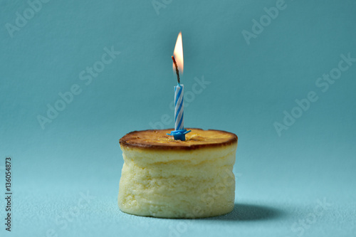 lit birthday candle on a cheesecake stock photo and royalty free