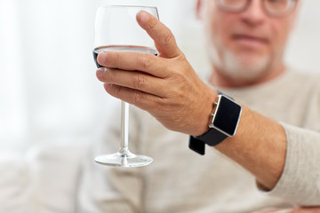senior man drinking red wine from glass at home