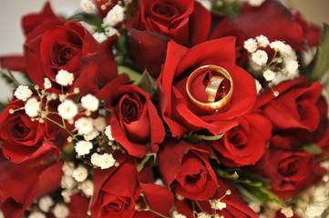 Trauringe in einem Strauß Rosen