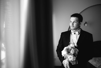 handsome groom with bouquet of flowers standing at home