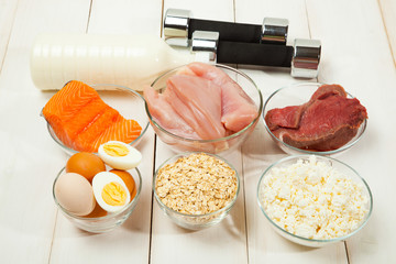 Protein diet, fish, cheese, eggs, meat, chicken and dumbbells on a white wooden background