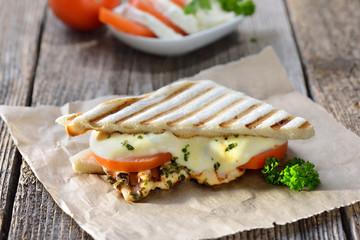 Streetfood: Italienisches Panini mit gegrillter Kräuter-Hähnchenbrust, Tomaten und Mozzarella - Toasted panini with grilled chicken breast fillet, tomatoes and melted mozzarella