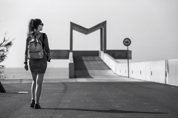 Young and attractive woman is walking away along the path in urb