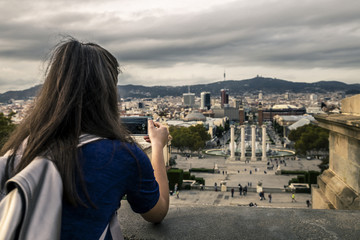 Young girl with long brown hair standing on view point and taking a picture of the city landscape using mobile phone. Backside view. Monjuic, Barcelona, Spain