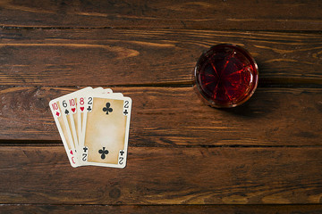 Playing cards and drink on the old boards
