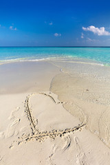 Waves wash away a heart drawn on sand of a tropical beach