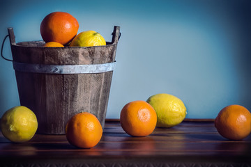 citrus fruit in a wooden bucket on a blue background