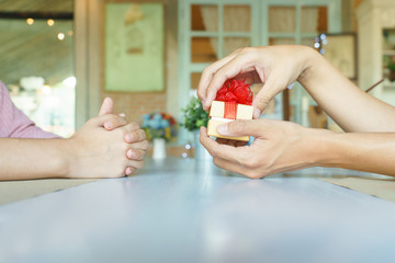 Man hands opening a golden present box with red ribbon to give