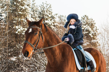 Small girl and horse in a winter