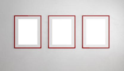 Drei rote Bilderrahmen hängen an Wand