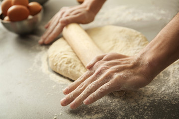 Man rolling out dough on kitchen table, close up