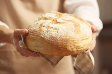 Male hands holding freshly baked wheaten bread, closeup