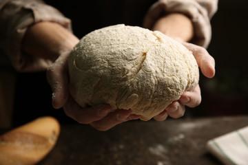 Hands holding dough ready for baking, closeup