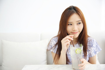 woman drinking lime juice in white coffeeshop