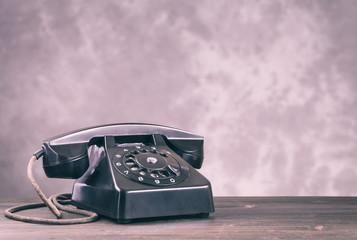 Old black phone on light