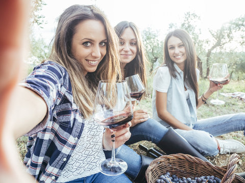 Three girlfriends take selfie in a field while drinking red wine after the grape harvest