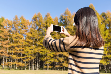 Woman taking photo by cellphone in autumn forest