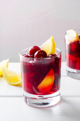 Cold drink with cherry and lemon in glasses, on white wooden background