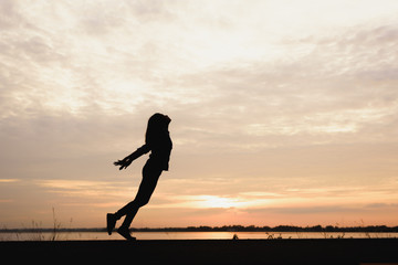 Silhouette of Woman breathing fresh air at sunset background.