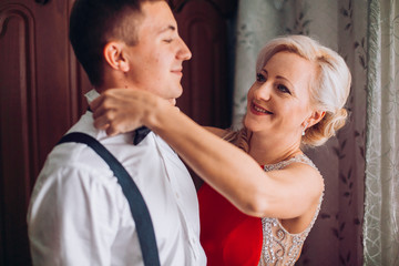 Mother is helping with a bow-tie to her son before wedding ceremony. Concept mother and son.