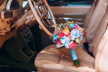 Wedding flowers colors bouquet with peones and hydrangea in retro car