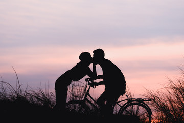 Silhouette couple kissing on bike over sunset background.