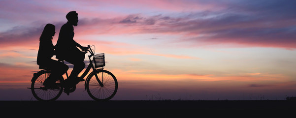Silhouette of couple on bike. panoramic banner background