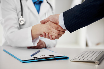 Female doctor in uniform shaking hands with businessman partner in the office.