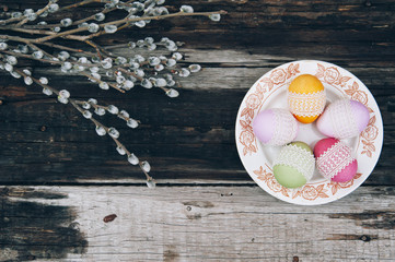 Colorful easter eggs decorated with white lace on the old wooden table background and some spring pussy willow