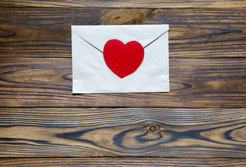 Love letter. Beautiful brown letter with red heart on wooden bac