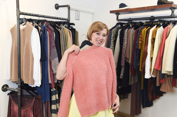 beautiful young woman shopping at fashion boutique choosing clothes smiling happy and satisfied