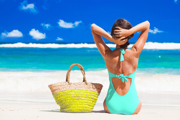 back view of a woman in bikini with beach bag