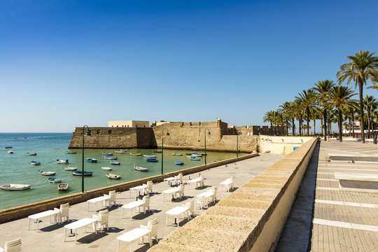 Seafront with view of medieval Castle of Santa Catalina, Cadiz (Spain).