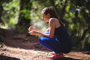 Woman in squatting position in forest walkway