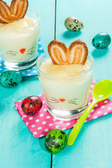 Funny food for children at Easter: dessert panna cotta (pudding) in the glass, decorated with a bunny, with ears of cookies, copy space