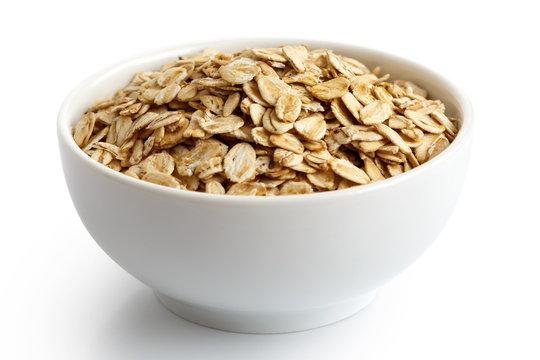 Dry porridge oats in white ceramic bowl isolated on white.