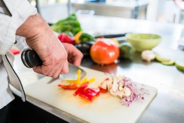 Koch oder Küchenchef schneiden Gemüse und Zwiebeln