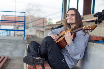 Young smiling Caucasian man playing the guitar sitting cross-leg