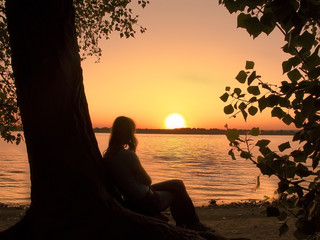 Silhouette of a girl sitting down and watching the sun setting over the river.
