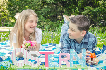 Children in the park with easter eggs in their hands and a decorative inscription Easter in German