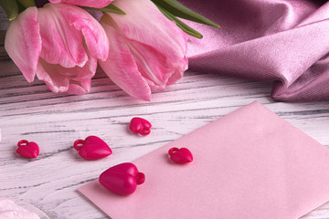 Valentine's day background with pink tulip flowers red hearts shape sign on white pink envelope on white wooden background.
